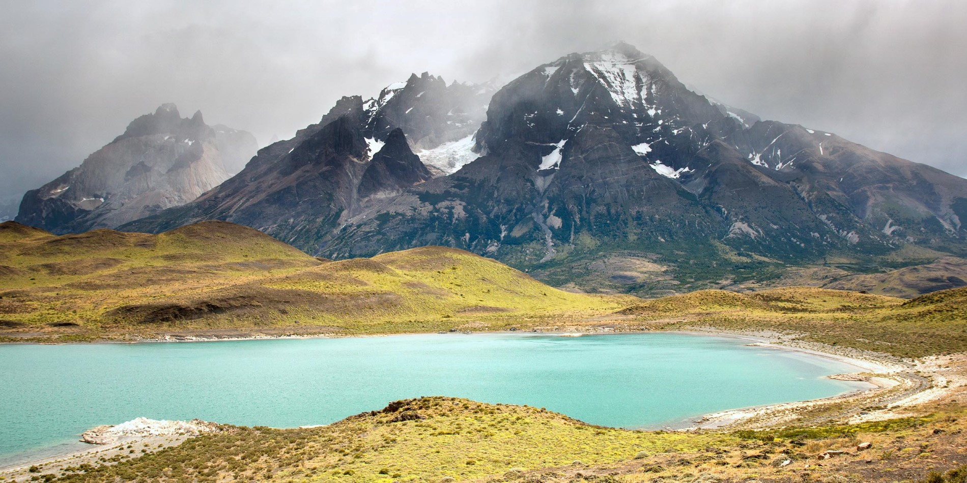 A body of water with Torres del Paine National Park in the background