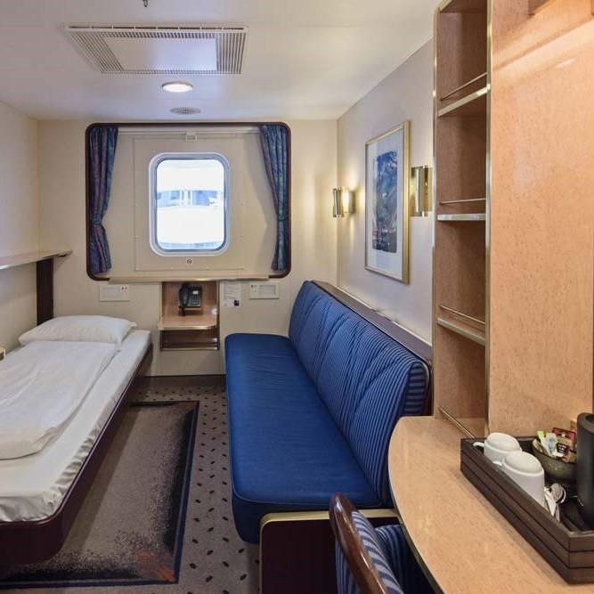 Ett sovrum med en säng och skrivbord i ett rum